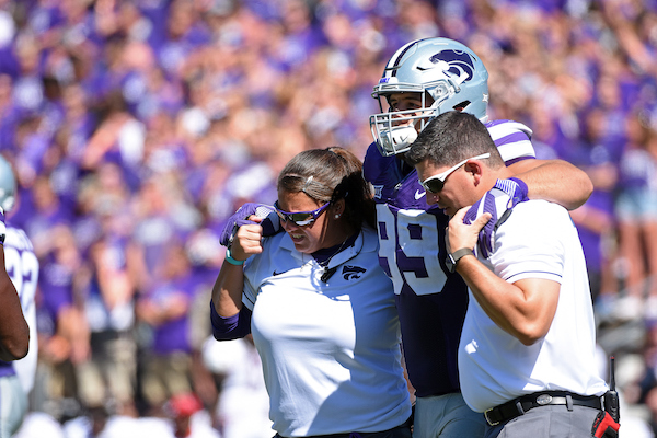 Dissinger Reed K-State | Matt Thomason and Mindy Hoffman help an injured K-State football player off the field